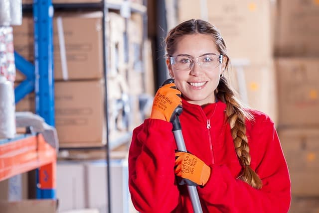 Woman smiling for picture holding a broom in a warehouse