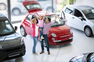 clean car dealership with family excited about new car